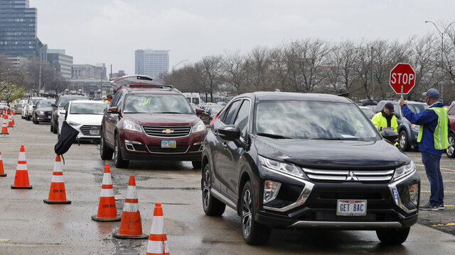 Cars line up to receive food at the Greater Cleveland Food Bank food distribution, Thursday, May 14, 2020, in Cleveland. (AP Photo/Tony Dejak)