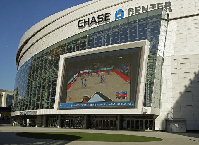 The Chase Center, home of NBA basketball's Golden State Warriors, show a pre-recorded video of a basketball game on a large screen at the entrance to the areana on a day the team was to play the Brooklyn Nets, Thursday, March 12, 2020, in San Francisco. The NBA suspended its season after a Utah Jazz player tested positive Wednesday for the coronavirus. (AP Photo/Ben Margot)