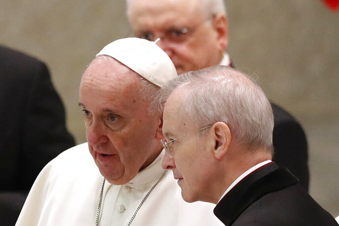 Pope Francis shares a word with Monsignor Luis Maria Rodrigo Ewart as he arrives in the Paul VI Hall at the Vatican for his weekly general audience, Wednesday, Oct. 28, 2020. A Vatican official who is a key member of Francis' COVID-19 response commission, the Rev. Augusto Zampini, acknowledged Tuesday that at age 83 and with part of his lung removed after an illness in his youth, Francis would be at high risk for complications if he were to become infected. Zampini said he hoped Francis would don a mask at least when he greeted people during the general audience.