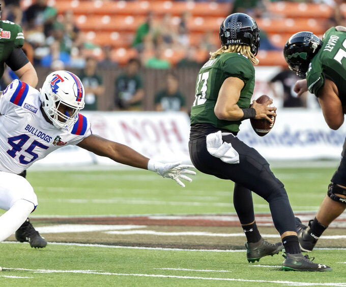 Louisiana Tech defensive end Jaylon Ferguson (45) reaches out to try and grab Hawaii quarterback Cole McDonald (13) in the first half of the Hawaii Bowl NCAA college football game, Saturday, Dec. 22, 2018, in Honolulu. (AP Photo/Eugene Tanner)