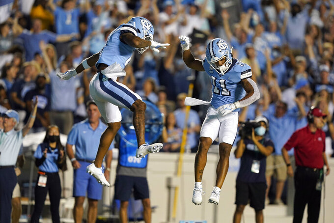 North Carolina wide receiver Emery Simmons, left, and wide receiver Josh Downs (11) celebrate Downs' touchdown against Virginia during the first half of an NCAA college football game in Chapel Hill, N.C., Saturday, Sept. 18, 2021. (AP Photo/Gerry Broome)