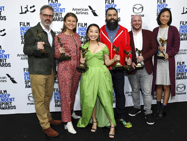 From left, Peter Saraf, Daniele Melia, Lulu Wang, Andrew Miano, Eddie Rubin, Anita Gou pose in the press room with the award for best feature for