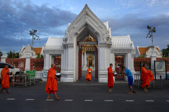 Monks wearing protective face masks stand outside the temple of the Emerald Buddha receiving alms from devotees at dawn in Bangkok, Thailand, Wednesday, May 27, 2020. The Sangha Supreme Council of Thailand has advised monks and novices to wear masks while receiving offerings from people to help combat the spread of COVID-19, and prohibited Buddhist temples from holding events. (AP Photo/Gemunu Amarasinghe)