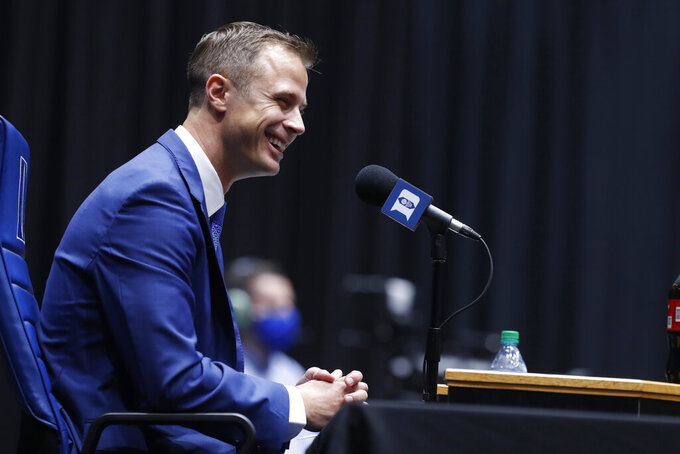 Jon Scheyer laughs during an NCAA college basketball press conference at Cameron Indoor Stadium in Durham, N.C., Friday, June 4, 2021. Scheyer will spend the upcoming year in his role as associate head coach as coach Mike Krzyzewski chases one more championship in a Hall of Fame career. Then it's up to the 33-year-old Scheyer to take over ahead of the 2022-23 season in the program's first coaching change in more than four decades. (Ethan Hyman/The News & Observer via AP)