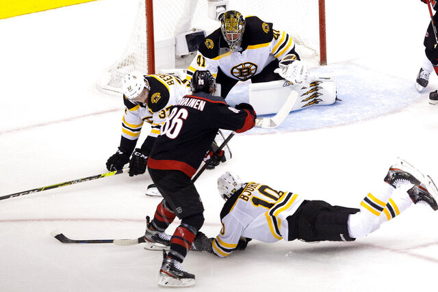 Boston Bruins' Patrice Bergeron (37) and Anders Bjork (10) try to block a shot from Carolina Hurricanes' Teuvo Teravainen (86) as Bruins goaltender Jaroslav Halak (41) looks on during first period NHL Eastern Conference Stanley Cup playoff game in Toronto on Saturday, Aug. 15, 2020.  (Chris Young/The Canadian Press via AP)