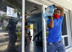 A man carries drinking water for a customer at a water depot store before the arrival of Hurricane Isaias in Freeport, Grand Bahama, Bahamas, Friday, July 31, 2020. (AP Photo/Tim Aylen)