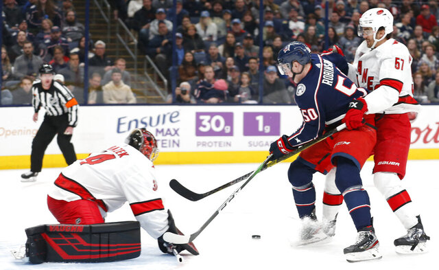 Carolina Hurricanes' Petr Mrazek, left, of the Czech Republic, makes a save as teammate Trevor van Riemsdyk, right, and Columbus Blue Jackets' Eric Robinson looks for a rebound during the second period of an NHL hockey game Thursday, Jan. 16, 2020, in Columbus, Ohio. (AP Photo/Jay LaPrete)