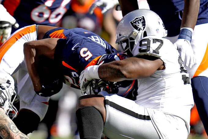 Denver Broncos quarterback Teddy Bridgewater (5) is sacked by Las Vegas Raiders defensive tackle Damion Square (97) during the first half of an NFL football game, Sunday, Oct. 17, 2021, in Denver. (AP Photo/Jack Dempsey)