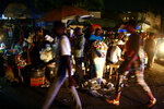 In this April 16, 2019 photo, vendors sit at a street corner as people walk past them, at night in Petion-Ville, Haiti. Since the blackouts hit Haiti, nighttime activity has ground to a halt as armed robbers hold up street merchants or break into people's homes in darkness. (AP Photo/Dieu Nalio Chery)