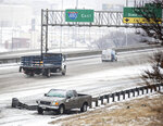 A pickup truck sits on the side of eastbound I-480 after an accident on slick roads on Monday, Jan. 25, 2021, in Omaha, Neb. The area is under a winter storm warning. (Chris Machian/Omaha World-Herald via AP)
