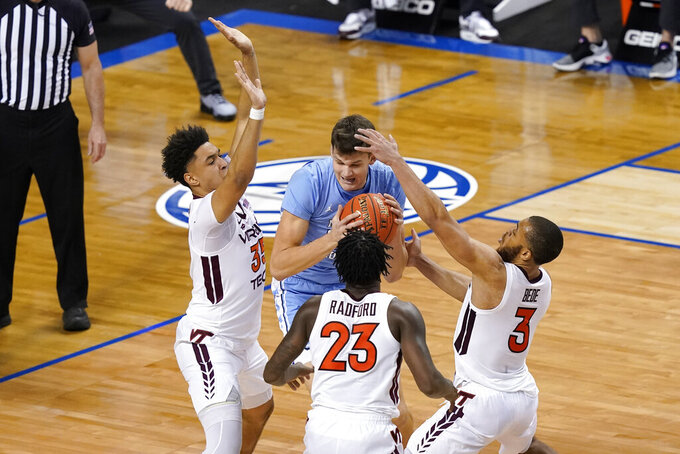 North Carolina forward Walker Kessler (13) protects the ball as Virginia Tech forward Cordell Pemsl (35) teammates guard Tyrece Radford (23) and guard Wabissa Bede (3) close in during the first half of an NCAA college basketball game in the quarterfinal round of the Atlantic Coast Conference tournament in Greensboro, N.C., Thursday, March 11, 2021. (AP Photo/Gerry Broome)