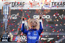 Kyle Larson shoots pistols as he celebrates in Victory Lane after winning the NASCAR Cup Series All-Star auto race at Texas Motor Speedway in Fort Worth, Texas, Sunday, June 13, 2021. (AP Photo/Tony Gutierrez)
