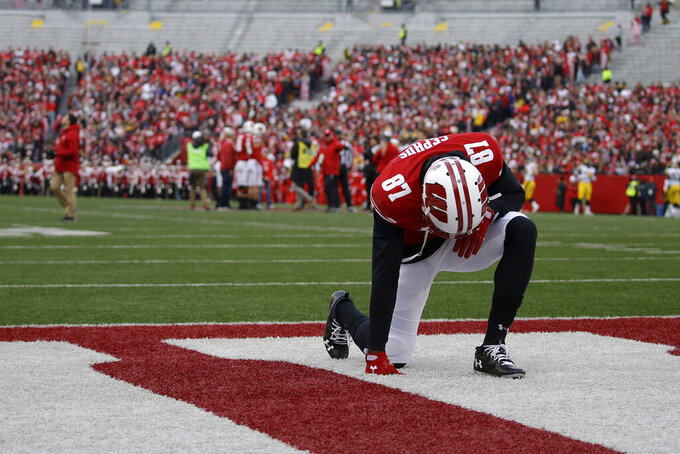 FILE - In this Nov. 9, 2019, file photo, Wisconsin's Quintez Cephus kneels before an NCAA college football game against Iowa, in Madison, Wis. Faith and family mean everything to Quintez Cephus. The junior wide receiver is enjoying the most productive season of his career at Wisconsin. But less than four months ago, football was gone, and all Cephus had was his faith and his family. (AP Photo/Aaron Gash, File)