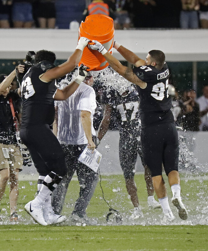 Central Florida head coach Josh Heupel, center, gets a sports drink dumped on him by players during final moments of the American Athletic Conference championship NCAA college football game against Memphis, Saturday, Dec. 1, 2018, in Orlando, Fla. (AP Photo/John Raoux)