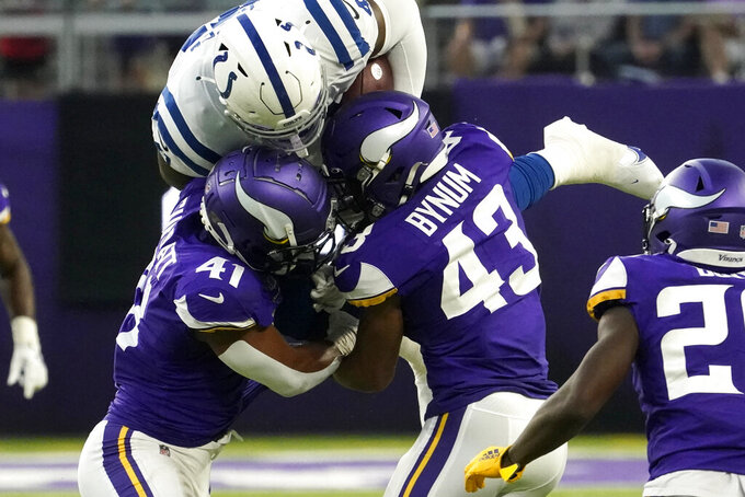 Indianapolis Colts tight end Farrod Green, center, is tackled by Minnesota Vikings linebacker Chazz Surratt, left, and cornerback Camryn Bynum, right, after catching a pass during the first half of an NFL football game, Saturday, Aug. 21, 2021, in Minneapolis. (AP Photo/Jim Mone)