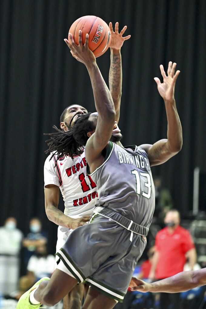UAB guard Quan Jackson (13) shoots in front of Western Kentucky guard Taveion Hollingsworth (11) in the second half of an NCAA college basketball game in the Conference USA men's tournament, in Frisco, Texas, Friday, March 12, 2021. Western Kentucky won 64-60. (AP Photo/Matt Strasen)