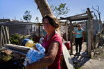 A woman carries donated bottled water in front of her home destroyed by last week's tornado in El Roble, on the outskirts of Havana, Cuba, Wednesday, Feb. 6, 2019. More than a week after a rare tornado struck Havana, the worst-hit neighborhoods are filled with government crews restoring power and phone service and starting repairs to devastated homes. (AP Photo/Ramon Espinosa)