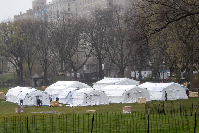 A Samaritan's Purse crew works on building an emergency field hospital specially equipped with a respiratory unit in New York's Central Park across from The Mount Sinai Hospital, Sunday, March 29, 2020. (AP Photo/Mary Altaffer, File)
