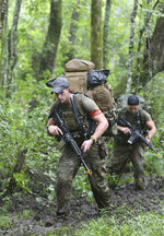Special Forces candidates assigned to the U.S. Army John F. Kennedy Special Warfare Center and School patrol through a wooded area during the final phase of field training known as Robin Sage in central North Carolina, July 9, 2019. Robin Sage is the culmination exercise and has been the litmus test for Soldiers striving to earn the Green Beret for more than 40 years. Commanders are making big changes to the grueling course that soldiers must pass to join the elite Special Forces. The goal is to meet evolving national security threats and to shift from a culture that weeds out struggling soldiers to one that trains them to do better. (Ken Kassens/U.S. Army via AP)