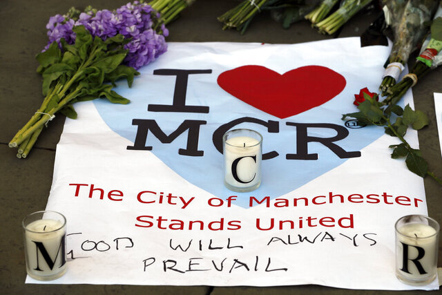 FILE- In this Tuesday May 23, 2017 file photo, a sign is seen with flowers and candles after a vigil in Albert Square, Manchester, England, the day after the suicide attack at an Ariana Grande concert that left 22 people dead. The younger brother of the suicide bomber who killed 22 people at an Ariana Grande concert in Manchester, England, was convicted Tuesday, March 17, 2020 of murder for helping to plan the attack. (AP Photo/Kirsty Wigglesworth, file)