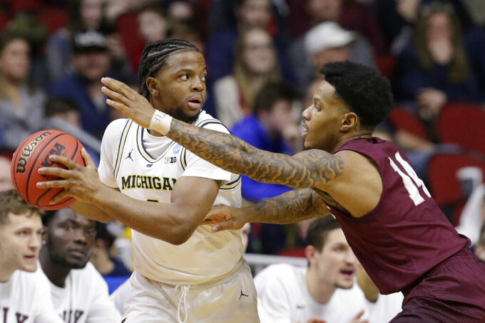 Michigan's Zavier Simpson, left, is defended by Montana's Ahmaad Rorie (14) during the first half of a first round men's college basketball game in the NCAA Tournament, in Des Moines, Iowa, Thursday, March 21, 2019. (AP Photo/Nati Harnik)