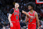 Chicago Bulls' Zach LaVine (8) acknowledges the play of first-round draft pick Coby White during the second half of an NBA basketball game against the New York Knicks Tuesday, Nov. 12, 2019, in Chicago. The Bulls won 120-102. (AP Photo/Charles Rex Arbogast)