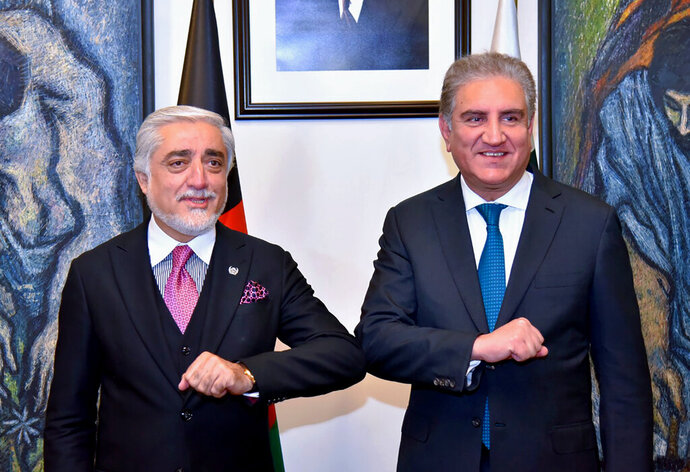 In this photo provided by Pakistan's Ministry of Foreign Affairs, Abdullah Abdullah, left, chairman of Afghanistan's High Council for National Reconciliation, bumps elbows with Pakistani Foreign Minister Shah Mahmood Qureshi, upon for a meeting, in Islamabad, Pakistan, Monday, Sept. 28, 2020. Afghanistan's top official in negotiations with the Taliban arrived in Pakistan's capital Monday on a three-day trip during which he will meet with the country's prime minister and other government officials. (Ministry of Foreign Affairs via AP)