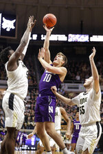 Northwestern forward Miller Kopp (10) shoots between Purdue's Trevion Williams (50) and Sasha Stefanovic during the first half of an NCAA college basketball game in West Lafayette, Ind., Sunday, Dec. 8, 2019. (AP Photo/Michael Conroy)