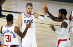 Los Angeles Clippers' Ivica Zubac, center, is congratulated by teammates Marcus Morris Sr. (31) and Paul George (13) during an NBA basketball game against the New Orleans Pelicans, Saturday, Aug. 1, 2020, in Lake Buena Vista, Fla. (Kevin C. Cox/Pool Photo via AP)