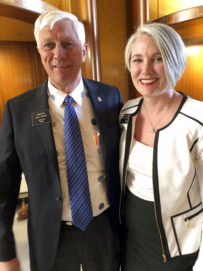 Sen. Jim Roers, left, and his daughter, Rep. Shannon Roers Jones, pose for a photo at the state Capitol in Bismarck, North Dakota, Tuesday, March 19, 2019. Roers Jones of Fargo pushed successful legislation to repeal the state's longstanding Sunday business restrictions that are rooted in religious tradition. Jim Roers voted against the repeal in 2017 but changed his mind after pressure from constituents and his daughter. (AP Photo/James MacPherson)