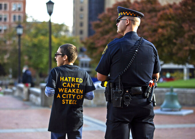 Sam Goldston, of Squirrel Hill, left, stands with police officer Andrew Hohol as people enter Soldiers and Sailors Memorial Hall and Museum for a public memorial service in Pittsburgh on Sunday, Oct. 27, 2019, honoring the lives of the 11 victims killed a year ago in the Tree of Life shooting. (Jessie Wardarski/Pittsburgh Post-Gazette via AP)