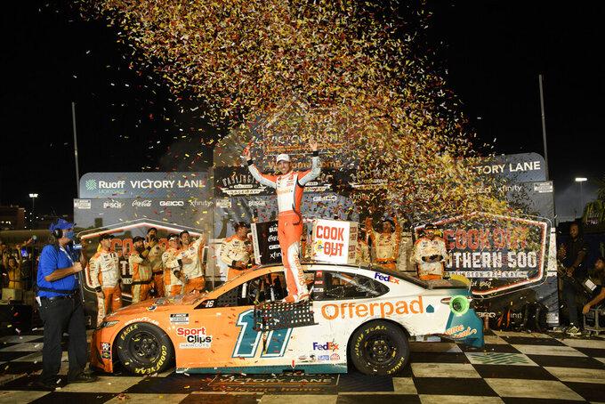 Denny Hamlin celebrates in victory lane after winning a NASCAR Cup Series auto race Sunday, Sept. 5, 2021, in Darlington, S.C. (AP Photo/John Amis)