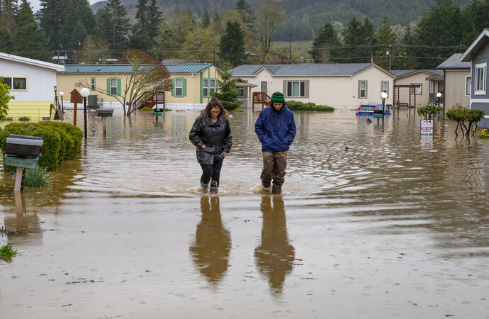 Shannon Archuleta, left, and her son Jett Archuleta wade through a flooded street in the Riverstone Mobile Home Park in Cottage Grove, Ore., Monday, April 8, 2019, to check on a family member after floodwaters rose overnight. (Chris Pietsch/The Register-Guard via AP)