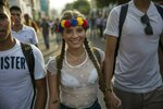 People walk to the Venezuela Aid Live concert that will play on the Colombian side of the border near the Simon Bolivar International Bridge, from San Antonio del Tachira, Venezuela, Friday, Feb. 22, 2019. Venezuela's power struggle is set to convert into a battle of the bands Friday when musicians demanding Nicolas Maduro allow in humanitarian aid and those supporting the embattled leader's refusal sing in rival concerts being held at both sides of a border bridge where tons of donated food and medicine are being stored. (AP Photo/Rodrigo Abd)