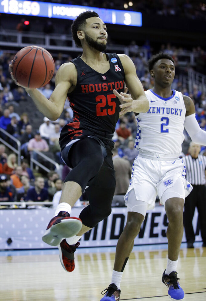 Houston's Galen Robinson Jr. (25) looks to pass around Kentucky's Ashton Hagans (2) during the first half of a men's NCAA tournament college basketball Midwest Regional semifinal game Friday, March 29, 2019, in Kansas City, Mo. (AP Photo/Charlie Riedel)