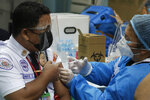 A security guard is inoculated with China's Sinovac COVID-19 vaccine at the Navotas Fish Port, Philippines on Monday, June 7, 2021. The government today bolstered its vaccination program by including frontline economic personnel both in private and government sectors. (AP Photo/Aaron Favila)
