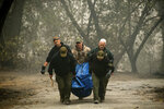 FILE - In this Saturday, Nov. 10, 2018 file photo, sheriff's deputies recover the remains of a victim of the Camp Fire on in Paradise, Calif. More than 2.7 million Californians live in areas that are at very high risk for wildfires. One in 12 homes in California are at high risk of burning in a wildfire. The more information we can share about where and how we're falling short, the quicker we can come together on potential solutions. (AP Photo/Noah Berger, File)