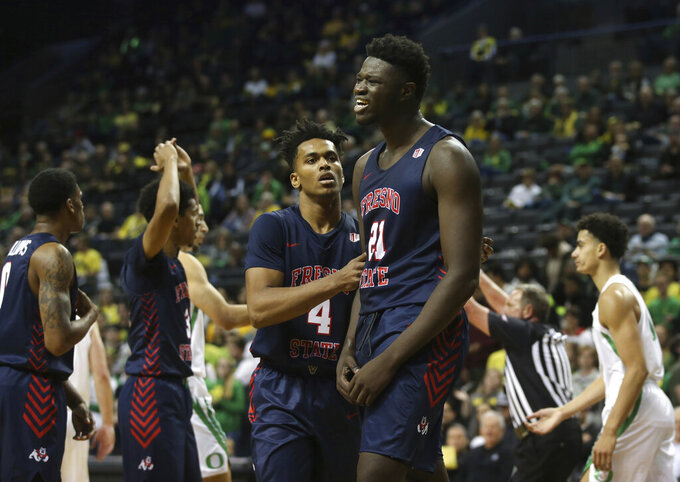Fresno State's Niven Hart, left, talks to Assane Diouf, who was called for a foul during the team's NCAA college basketball game against Oregon in Eugene, Ore., Tuesday, Nov. 5, 2019. (AP Photo/Chris Pietsch)