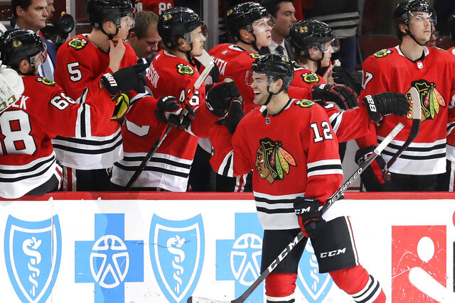 Chicago Blackhawks left wing Alex DeBrincat (12) celebrates with teammates after scoring a goal during the second period of an NHL hockey game against the Edmonton Oilers in Chicago, Thursday, March 5, 2020. (AP Photo/Nam Y. Huh)