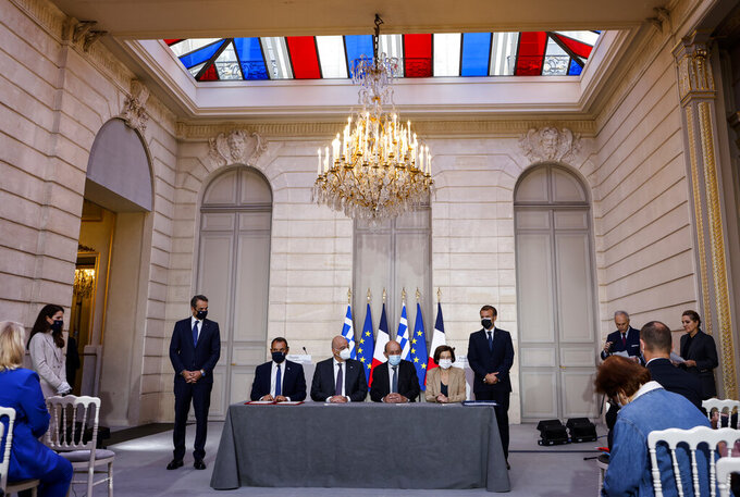 From the left, Greek Prime Minister Kyriakos Mitsotakis, Greek Defence Minister Nikolaos Panagiotopoulos, Greek Foreign Affairs Minister Nikos Dendias, French Foreign Affairs Minister Jean-Yves Le Drian, French Defense Minister Florence Parly and French President Emmanuel Macron take part in the signing ceremony of a new defence deal at The Elysee Palace Tuesday, Sept. 28, 2021. France and Greece announced on Tuesday a major, multibillion-euro defense deal including Athens' decision to buy three French warships. (Ludovic Marin, Pool Photo via AP)