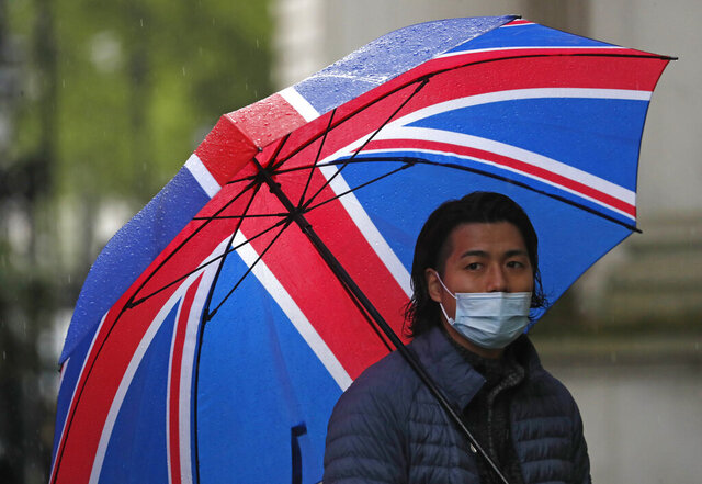 A journalist wearing a face mask to protect against coronavirus shelters under a Union flag umbrella outside 10 Downing Street in London, Tuesday, April 28, 2020. (AP Photo/Frank Augstein)