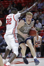 Utah center Lahat Thioune (32) defends against UC Davis forward Kennedy Koehler (10) during the first half during an NCAA college basketball game Friday, Nov. 29, 2019, in Salt Lake City. (AP Photo/Rick Bowmer)
