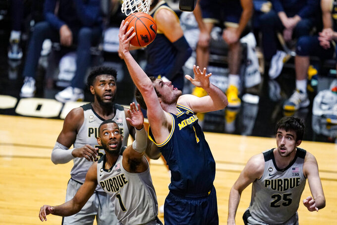 Michigan center Hunter Dickinson (1) shoots between Purdue forward Aaron Wheeler (1) and guard Ethan Morton (25) during the second half of an NCAA college basketball game in West Lafayette, Ind., Friday, Jan. 22, 2021. Michigan won 70-53. (AP Photo/Michael Conroy)