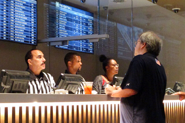 In this Sept. 5, 2019 photo, a gambler places sports bets at Bally's casino in Atlantic City, N.J. New Jersey gambling regulators have approved wagering on the XFL, becoming the sixth state to approve bets on the revived football league that last operated in 2001. Its season begins Feb. 8, 2020. (AP Photo/Wayne Parry)