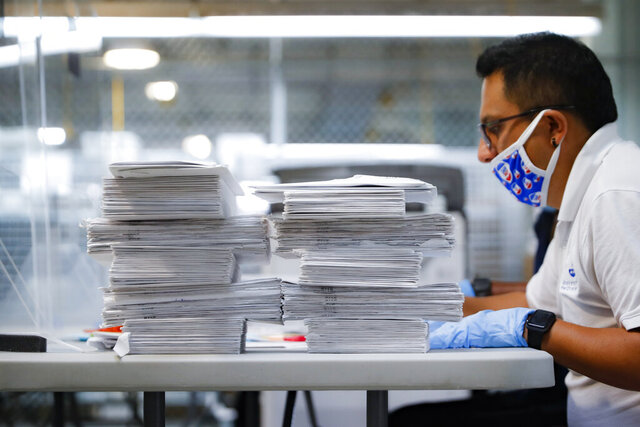Stacks of ballots are prepared to be checked by a worker at a Board of Elections facility, Wednesday, July 22, 2020, in New York. A federal judge sided with the challenger in a tight New York City Democratic congressional primary and ruled that at least 1,000 disputed ballots should be counted. (AP Photo/John Minchillo)