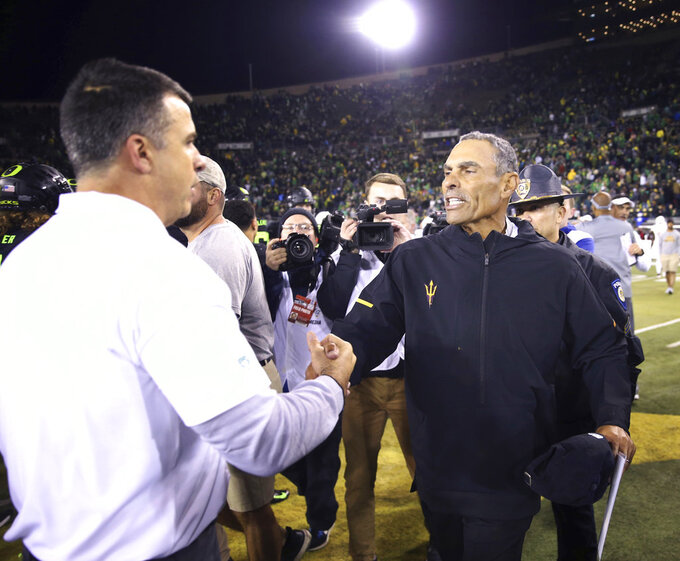 Oregon head football coach Mario Cristobal, left, meets Arizona State head football coach Herm Edwards at midfield after the Duck's won the game 31-28 in an NCAA college football game Saturday, Nov. 17, 2018, in Eugene, Ore. (AP Photo/Chris Pietsch)