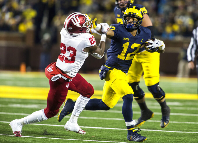 Michigan running back Chris Evans (12) holds his arm out to keep away Indiana defensive back Jaylin Williams, in the third quarter of an NCAA college football game in Ann Arbor, Mich., Saturday, Nov. 17, 2018. Michigan won 31-20. (AP Photo/Tony Ding)
