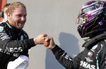 Mercedes driver Valtteri Bottas of Finland, left, is congratulated with a fist bump by Mercedes driver Lewis Hamilton of Britain after clocking the fastest time during qualification ahead of Sunday's Emilia Romagna Formula One Grand Prix, at the Enzo and Dino Ferrari racetrack, in Imola, Italy, Saturday, Oct. 31, 2020. (AP Photo/Luca Bruno, Pool)