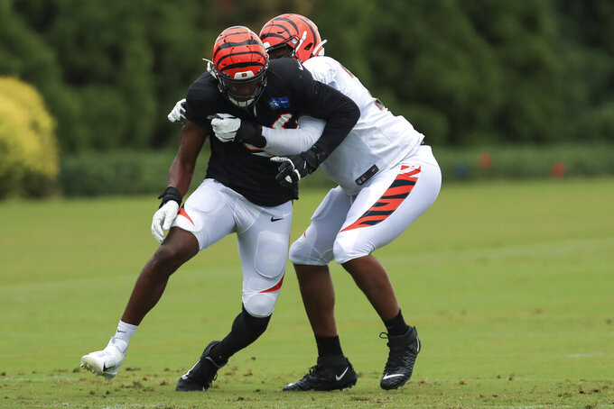 Cincinnati Bengals' Carlos Dunlap, left, rushes against Fred Johnson, right, during an NFL football camp practice in Cincinnati, Tuesday, Aug. 18, 2020. (AP Photo/Aaron Doster)