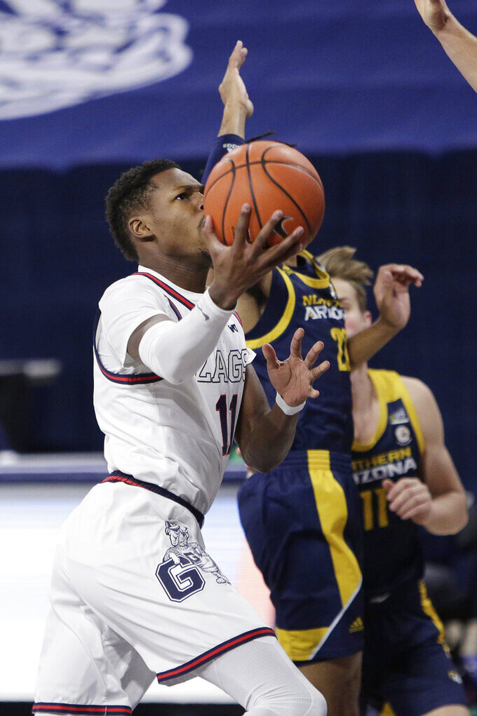 Gonzaga guard Joel Ayayi, left, shoots next to Northern Arizona guard Cameron Shelton during the first half of an NCAA college basketball game in Spokane, Wash., Monday, Dec. 28, 2020. (AP Photo/Young Kwak)